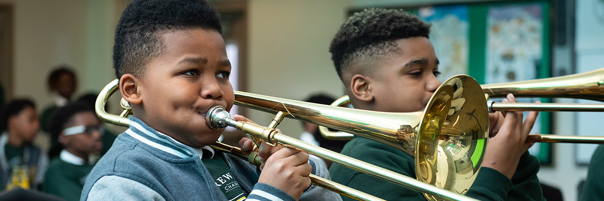 Two male students playing trombones in band class